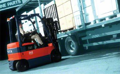 Heftruck die de goederen aan de zijkant van de vrachtwagen afhandelt