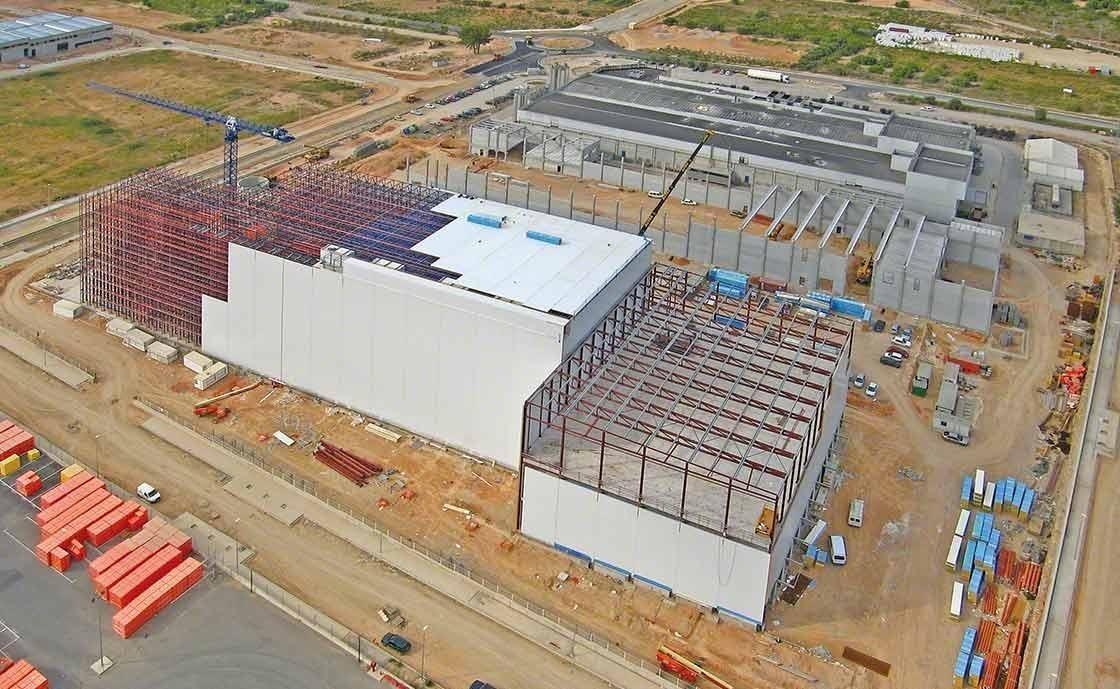 Construction d'un entrepôt avec rayonnages autoportants intégrés, résistants aux tremblements de terre et aux fortes rafales de vent.