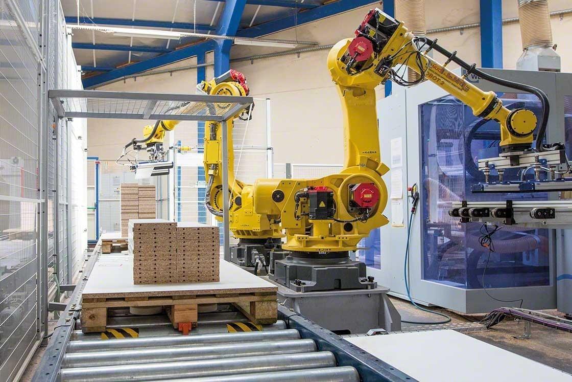 Des bras mécanisés qui réalisent la palettisation des marchandises dans un entrepôt robotisé.
